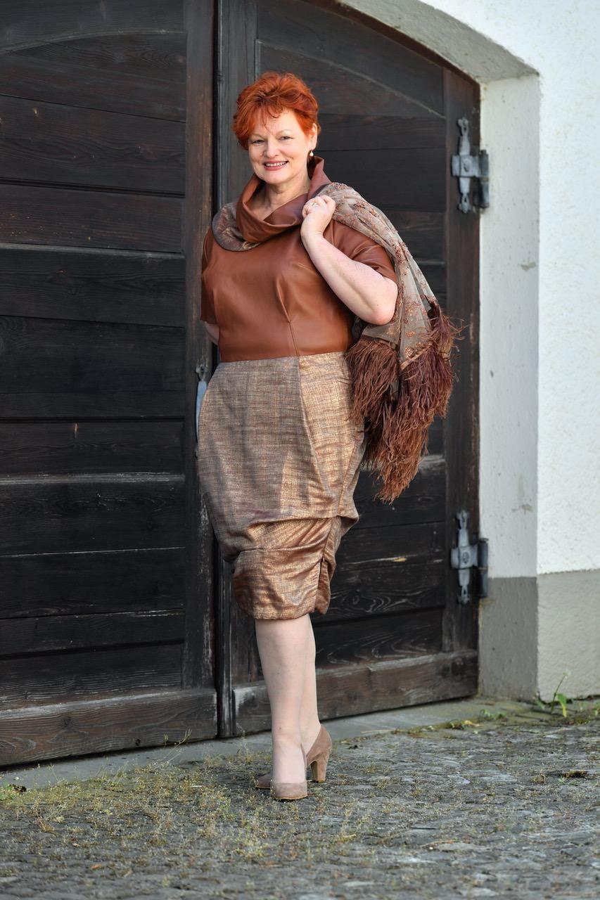 Kleid mit Lederoberteil, trapiertem Rock und Stickereiumhang